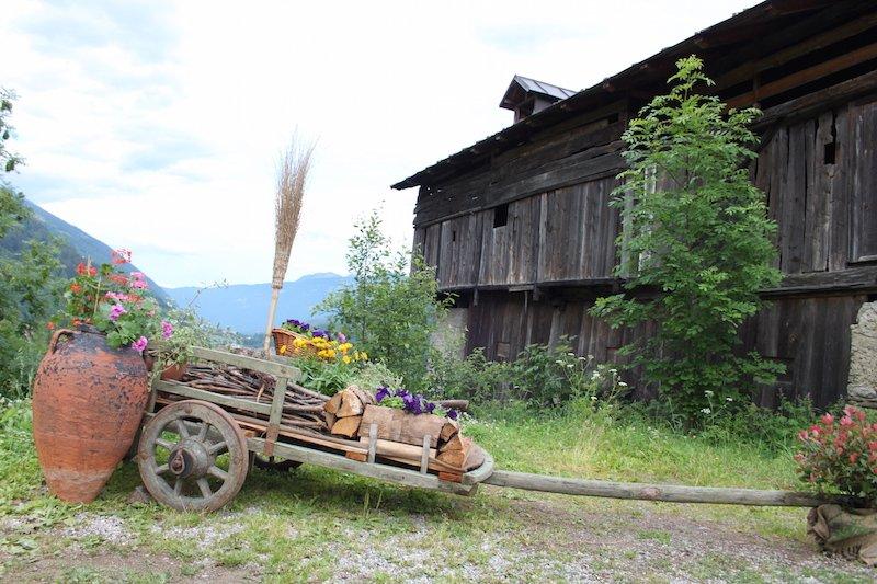 un maso, tipica struttura antica della Val di Sole con davanti un carro di legno, oggi bello da ornare con i fiori