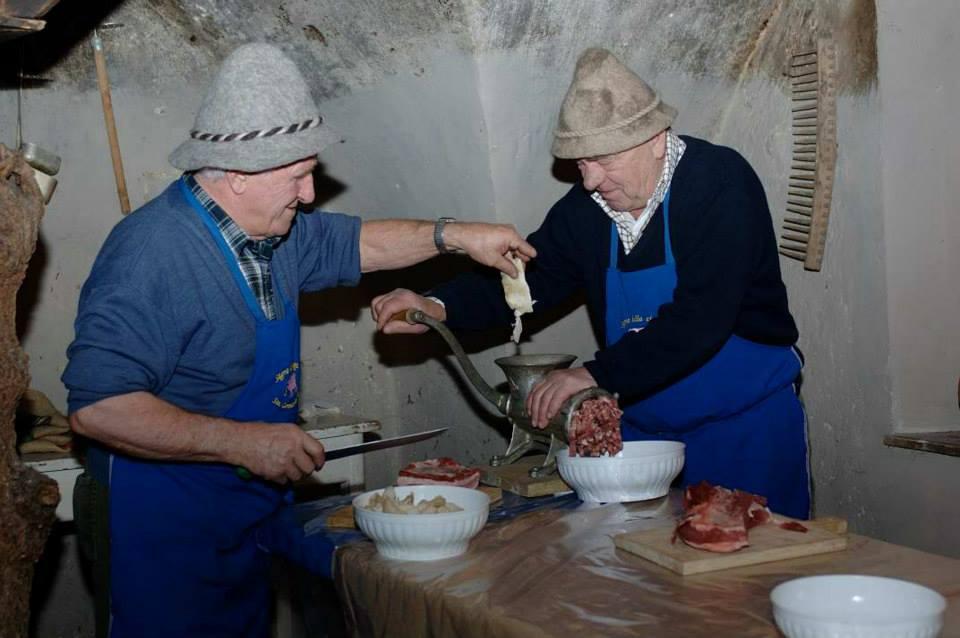 due anziani signori preparano tradizionalmente la ciuiga del banale