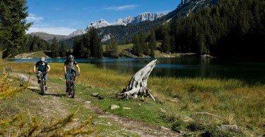 pedalando in riva al lago con le Dolomiti alle spalle