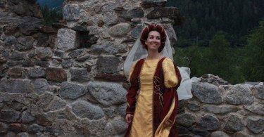Una dama tra le mura del castello di Ossana sorride entusiasta