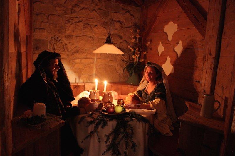 una coppia di figuranti cena a lume di candela nel privè