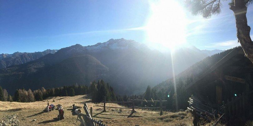 dietro il sole la cima Presanella e la cima Vermiglio